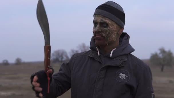 Egy dühös mutamt szörny dobja fel nagy machete és spinning a pusztaságot. Horror karakter fogalma, a fegyveres és a grasepainted egység