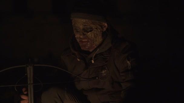 Ronda veszélyes zombi szörny ülve közelében a tábortűz nehéz kereszt íj sötét romos beton menedéket. Horror karakter koncepció, a fegyveres és grasepainted egység