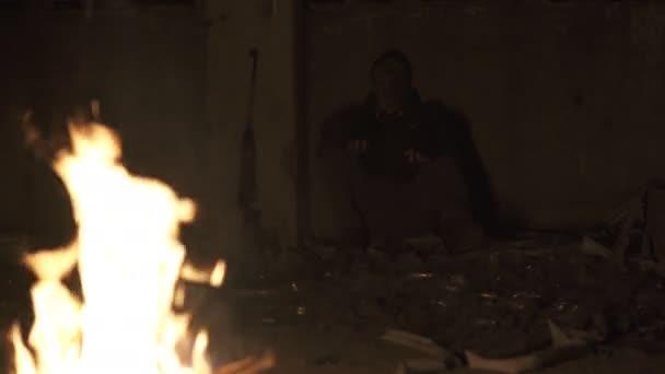 Ronda veszélyes zombi szörny ülve közelében a tábortűz a puska a Dark tönkrement beton menedéket. Horror karakter koncepció, a fegyveres és grasepainted egység