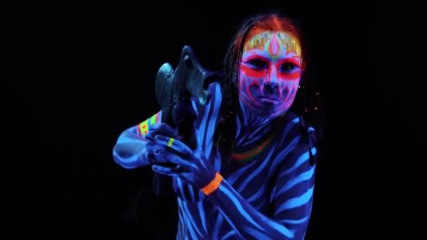 Portré fiatal csupasz bodyarted Savage nő, kék izzó ultraibolya festék ősi műalkotást Tomahawk fegyver. Agressive avatar harcos Amazon Pigtailek frizura