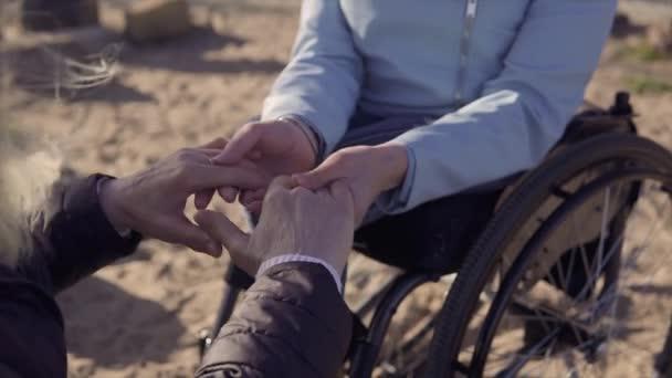 Familienfreizeit. junge behinderte Frau im Rollstuhl spricht mit ihrer Mutter, die am Meer sitzt und sich gegenseitig an den Händen hält