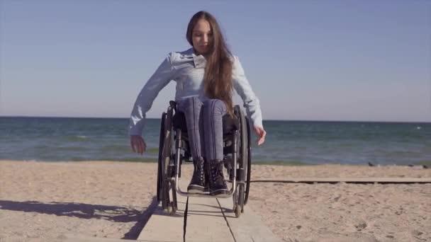 Mladá zdravotně postižené ženy v invalidním vozíku pohybující se na dřevěné rampě pro tělesně postižené v blízkosti moře na jaře nebo na podzim