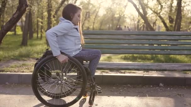 junge hübsche behinderte Frau im Rollstuhl, die abends im Park von ihrem Stuhl auf das Bankett steigt