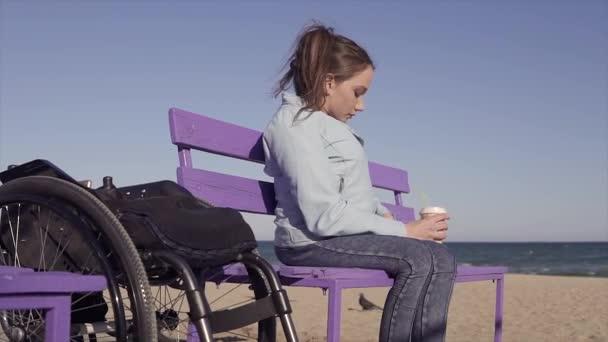 Junge hübsche behinderte Frau im Rollstuhl, die sich am Sandstrand in der Nähe des Meeres von ihrem Stuhl aufs Bankett bewegt und Kaffee trinkt