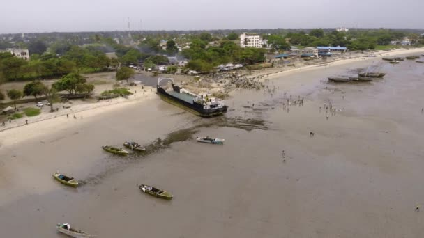 An aerial Flyby shot of Crowd of African people on a Low Tide at the Beach of Bagamoyo, Tanzania