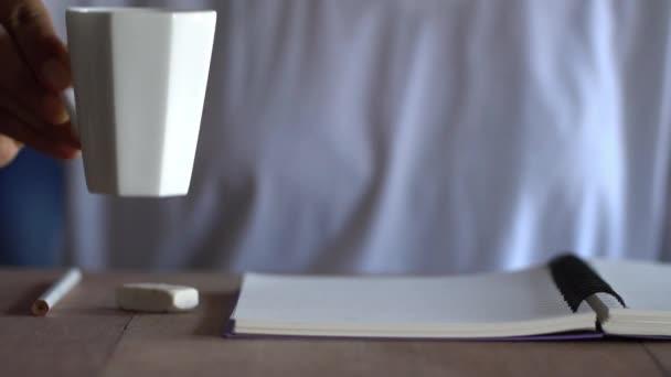 Fehér pólót viselő nők kávét iszik, és írás egy notebook barna fa tábla.