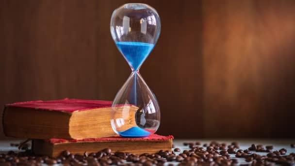 Időközű homok óra a régi könyvet, és kávét vetőmag a fából készült asztal. Hely másolása a szöveghez. Fogalma idő olvasni könyveket.