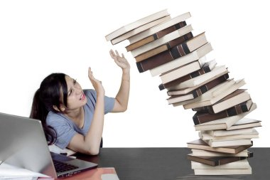 Picture of a Caucasian female college student holding a pile of falling books while studying in the studio