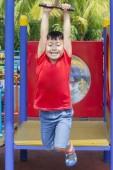 Porträt eines entzückenden kleinen Jungen sieht glücklich aus, während er auf dem fliegenden Fuchs gleitet. Schuss auf dem Spielplatz