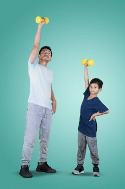 Full length of an Asian man with his son lifting a dumbbell while exercising together in the studio
