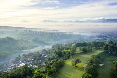 Aerial view of misty Bandung cityscape with crowded houses and golf course, West Java, Indonesia