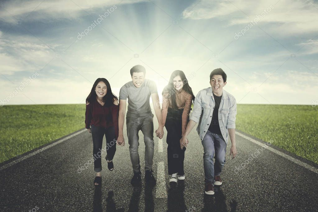 Young people hold hands and walk on the road