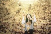 Cheerful woman playing with dried autumn leaves