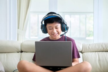 Preteen boy looks happy while using a laptop and headphones on the couch at home