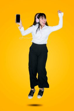 Businesswoman dancing and jumping in the studio while listening music with a mobile phone and headphones against yellow background