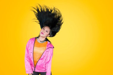 Female hip-hop dancer with long hair dancing in the studio against yellow background