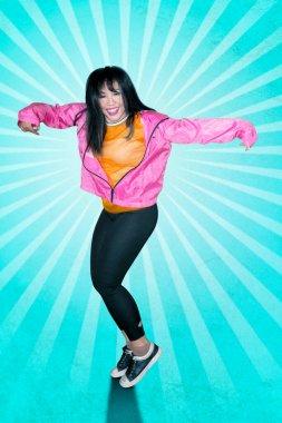 Joyful female hip-hop dancer is dancing with blue background in the studio