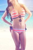 Sommerferienkonzept. Nahaufnahme einer schlanken Frau, die Badebekleidung mit Sonnenbrille trägt, während sie am Strand mit Sonnenlicht steht