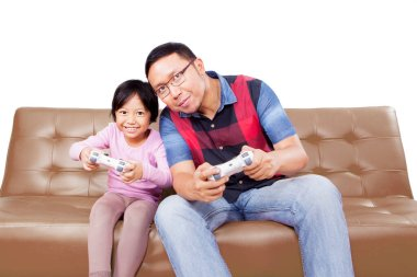 Happy little girl and her father playing video games together with joysticks while sitting on the sofa in the studio, isolated on white background stock vector