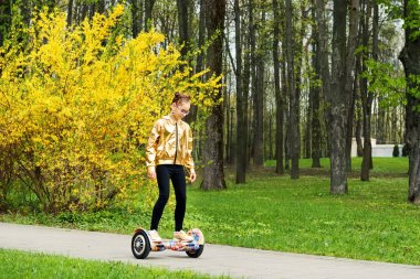 active girl in a gold jacket rides balances on self balancing scooter