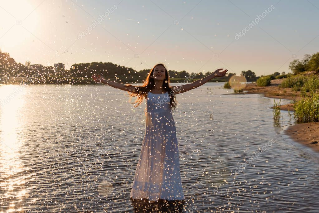 an immature young girl in a white wet dress is standing in a river and sprinkles water droplets up in the rays of the rising sun