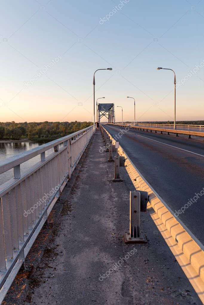 road across the bridge over the river in the rays of the sunset