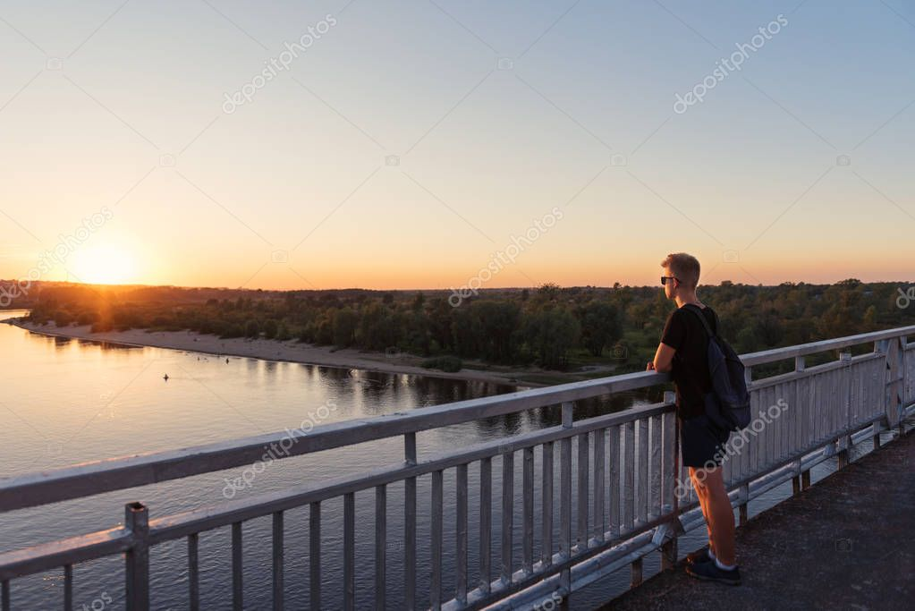 teenager guy in life style clothes standing near railings on bridge looking at sunset