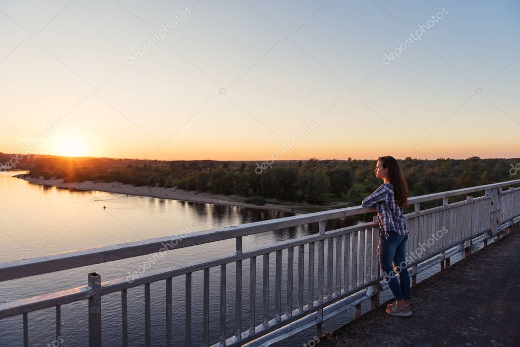 girl teenager in plaid shirt and jeans stands on a motu on the river with a view of the sunset