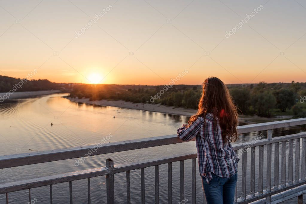 on a pier with steel railing over water stands girl young woman with her back with curly hair at sunset