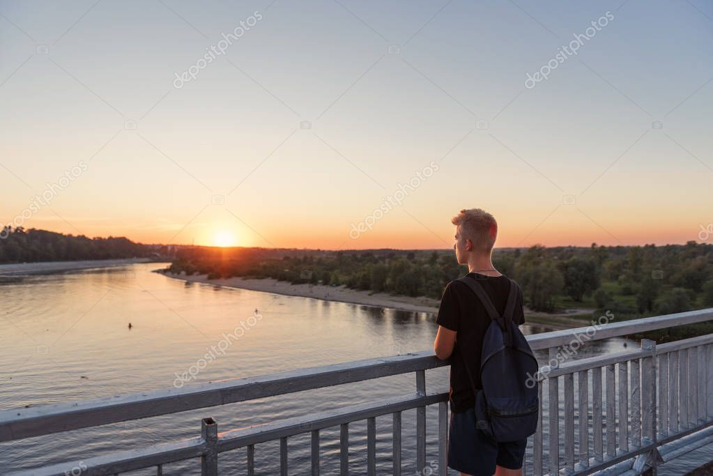 young guy teenager standing on bridge over river water in lifestyle clothes near steel railing and looking afar at sunset