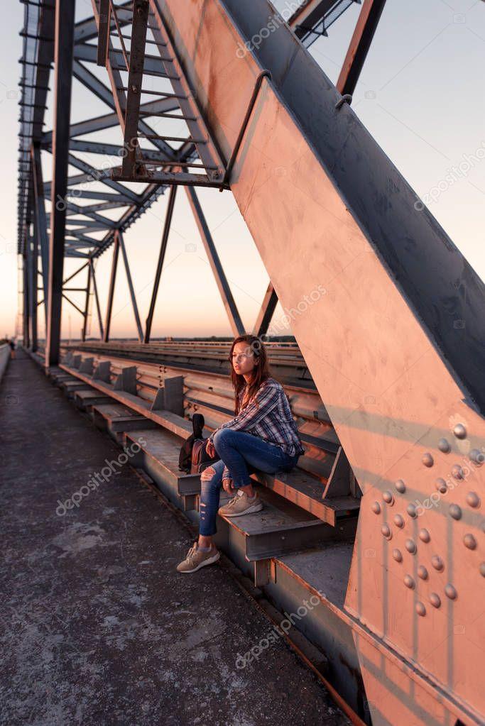 teen girl wanderer sitting on steel bridge design in docks and looking away at sunset