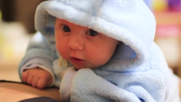 Smiling little baby girl with big blue eyes lying on her tummy on white bed looking at camera and smiling1