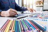 Obrázek mužského kreativního grafika pracujícího na výběru barev a kreslení grafického tabletu na pracovišti s pracovními nástroji a příslušenstvím.