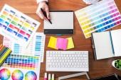 Podoba mužského kreativní grafik pracuje na výběr barvy a kresby na grafický tablet na pracovišti s pracovní nástroje a příslušenství, pohled shora.