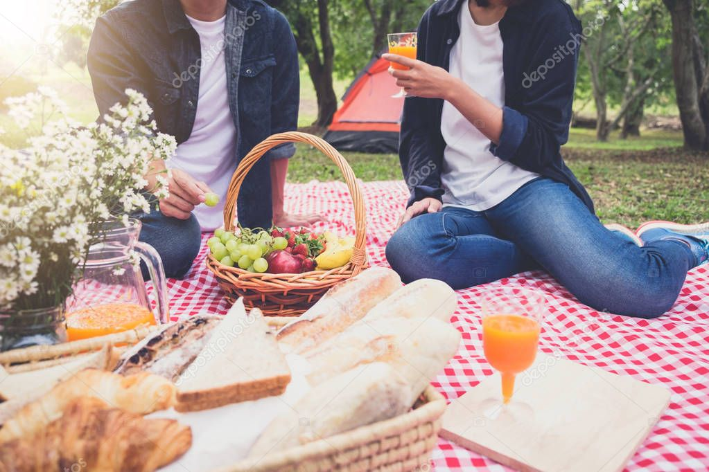 Couple in love drink a orange juice and fruits on summer picnic, leisure, holidays, eating, people and relaxation concept.