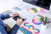 Mužské kreativní grafik pracující na výběr barvy a vzorky barev na grafický tablet na pracovišti s pracovní nástroje a příslušenství.