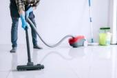 Hauswirtschaft und Reinigungskonzept, glücklicher junger Mann in blauen Gummihandschuhen mit Staubsauger auf dem Boden zu Hause.