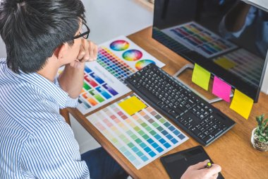 Image of male creative graphic designer working on color selection and drawing on graphics tablet at workplace with work tools and accessories in workspace.