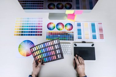 Male creative graphic designer working on color selection and color swatches, drawing on graphics tablet at workplace with work tools and accessories, top view workspace. stock vector