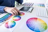 Férfi kreatív grafikai tervező dolgozik a színválasztás és Színtárak támaszkodva grafikus tábla, a munkahely, a munkaeszközök és kiegészítők.