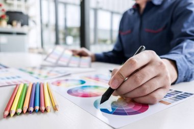 Image of male creative graphic designer working on color selection and drawing on graphics tablet at workplace with work tools and accessories. stock vector