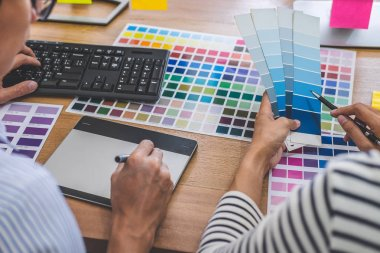 Two colleagues creative graphic designer working on color selection and drawing on graphics tablet at workplace, Color swatch samples chart for selection coloring. stock vector