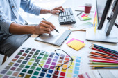 Obrázek mužského kreativního grafika pracujícího na výběru barev a kreslení grafického tabletu na pracovišti s pracovními nástroji a příslušenstvím na pracovišti.