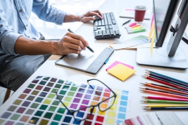 Image of male creative graphic designer working on color selection and drawing on graphics tablet at workplace with work tools and accessories in workspace. stock vector