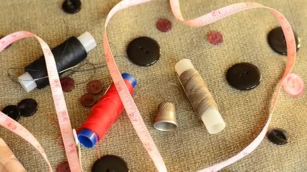 Zubehör zum Nähen: Nadeln, Fäden, Knöpfe, ein Fingerhut und ein Maßband auf grauem Hintergrund