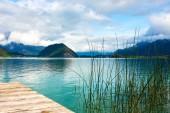 Fotografie See Wolfgagsee in Österreich in der Nähe von Salzburg mit Pier und Wasser Rasen, mit Bergen im Hintergrund unter blauem Himmel mit Wolken