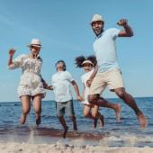 mladá africká americká rodina drží za ruce a skákání na pláži slunečného dne