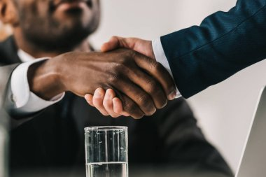 Cropped shot of african-american businessmen shaking hand stock vector