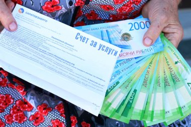 A bill for services and new Russian banknotes in the hands of an elderly woman close-u