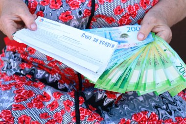 Receipt for light and new Russian banknotes in the hands of an elderly woma